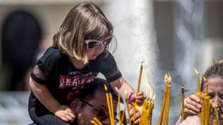 A little girl lights a candle for Easter in Skopje