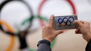 Turista tira foto nos anéis olímpicos instalados na praia de Copacabana