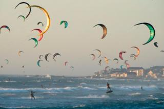 Kite surfers kitesurf in good wind and weather on February 6, 2019, in Tableview, about 15km from the centre of Cape Town.