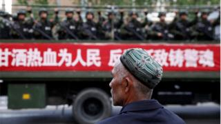 Uighur looks at military police in Xinjiang