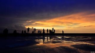 Fishermen stand along the seafront during sunset