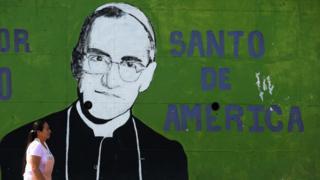 Imagem mostra mulher passando em frente à parede pintada com imagem do monsenhor Oscar Arnulfo Romero, o novo santo da Igreja