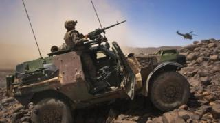 A French soldiers stands guard in an armoured vehicle as a helicopter leave a position in Mali. File photo
