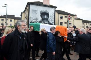 Sinn Fein President Gerry Adams (watches on as mourners carry the coffin of the late Martin McGuinness past the murals at Free Derry corner on 23 March 2017 in Northern Ireland.