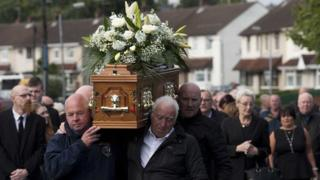 Mourners carry the coffin of Seamus Wright at his funeral