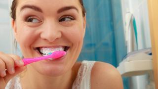 mulher escova os dentes