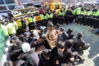 """Gente alrededor de la estatua de una """"mujer de confort"""" colocada frente a la embajada de Japón en Busán, Corea del Sur."""