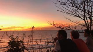 बाली द्वीपमा सूर्यास्त हेर्दै पर्यटकहरू