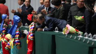 Moon Jae-in talks to a small North Korean child