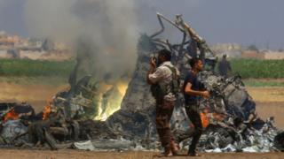 İdlib'de düşürülen helikopterin enkazı yanarken görülüyor.