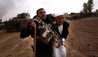 """Военнослужащий """"Золотой дивизии"""" уводит пожилого мужчину с места перестрелки с джихадистами в Тоб Зойе"""