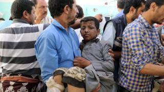 Homem iemenitas carrega criança feria em ataque aéreo em Saada, no Iêmen (9 agosto de 2018)