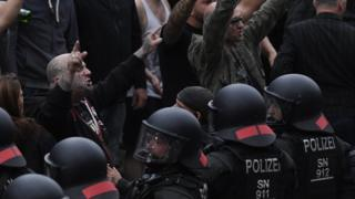 Right wing protesters gesture towards police in riot gear as they gather at the place where a man was stabbed