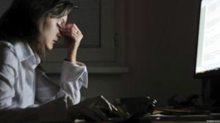 Mulher em frente ao computador parece estressada, com os olhos fechados e os dedos sobre os olhos
