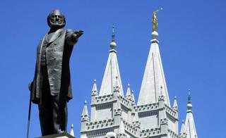 A statue of Brigham Young, second president of the Church of Jesus Christ of Latter Day Saints stands in the center of Salt Lake City with the Mormon Temple spires in the background