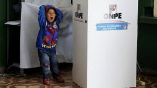 A child yawns while his mother casts her vote behind a voting booth in Peru's presidential election at a polling station in Lima, Peru, June 5, 2016.