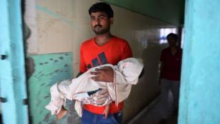 Hombre con niño en brazos saliendo del hospital Baba Raghav Das Hospital en Gorakhpur, en el estado de Uttar Pradesh en el Norte de la INdia, donde murieron 60 menores en 6 días.