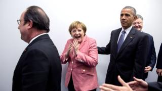 Angela Merkel, centre, laughs expressively with hands to her mouth, while Francois Hollande, left, and Mr Obama, right, remain impassive.