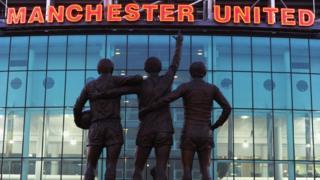 Les statues de George Best, Denis Law et Bobby Charlton devant le stade de Manchester United, 2e du championnat.