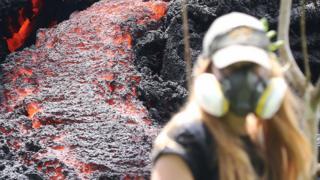 Una mujer camina junto a una fisura causada por la irupción del volcán Kilauea.