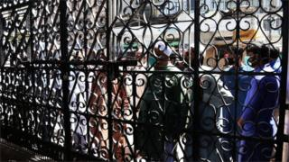 People wait outside a mosque to offer Friday congregational prayers despite a complete lockdown of the Sindh province in Karachi, Pakistan, 27 March 2020