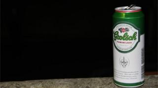 A can of Grolsch lager on a wall at night