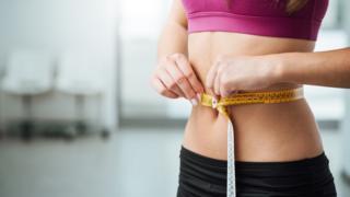 Mujer midiéndose la cintura.