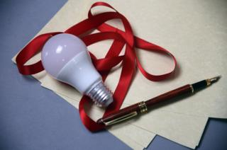 A light bulb, ribbon and a pen