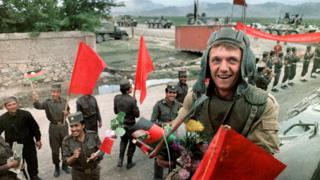 A Red Army soldier atop of his armoured personal vehicle smiles 16 May 1988 as Soviet Army troops stop in Kabul prior to their withdrawal from Afghanistan. The Soviet war in Afghanistan, also known as the Soviet-Afghan War, was a nine-year conflict involving Soviet forces supporting the Marxist People's Democratic Party of Afghanistan (PDPA) government against the Mujahideen resistance. The initial Soviet deployment of the 40th Army in Afghanistan began on August 7, 1978. The final troop withdrawal began on May 15, 1988, and ended on February 15, 1989.