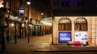 Homeless people sleep outside a theatre in central London
