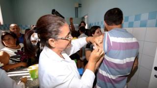 Profissional de saúde aplica vacina em homem de costas; ambos estão rodeados por outros pacientes dentro de sala ambulatorial