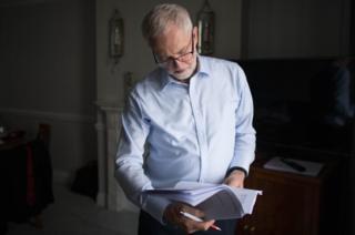 Jeremy Corbyn reads from a notebook.