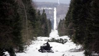 U.S. Border Patrol Agent Andrew Mayer rides a ATV as he looks for signs of illegal entry along the boundary marker cut into the forest marking the line between Canadian territory on the right and the United States near Beecher Falls, Vermont.