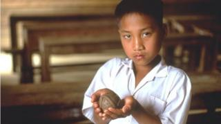"""A young Laotian boy holds a model of a """"bombie,"""" or cluster munitions"""