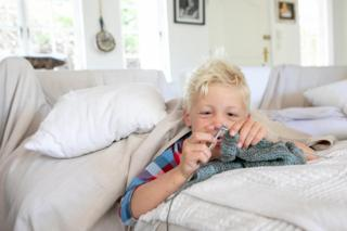 A boy lies on a bed and does some knitting