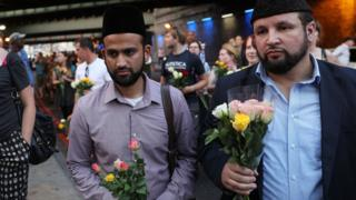 Men bring flowers to the vigil in Finsbury Park