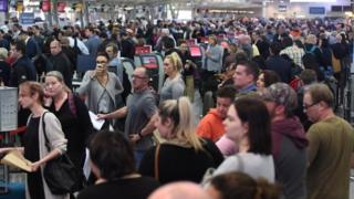A large crowd of passengers queue up at Sydney Airport on Monday