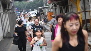 People walk in an alley behind a commercial district in Beijing.