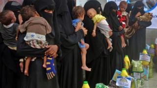Mujeres haciendo fila para recibir alimentos