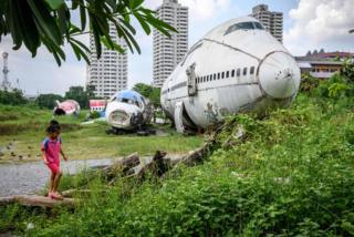 A child plays in front of abandoned aircraft in the suburbs of Bangkok on 9 October 2019. The area, known as the