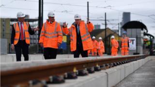 Boris Johnson walking alongside a tram track