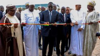 Senegal's President Macky Sall (C) is watched by his wife Marieme Faye Sall (R) and regional leaders as he cuts a ceremonial ribbon at the opening ceremony for the new Blaise Diagne International Airport - 7 December