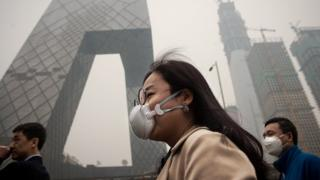 A woman wearing a protective pollution mask walks on a street in Beijing on March 20, 2017
