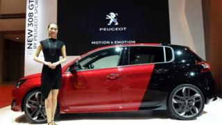 woman in front of Peugeot car