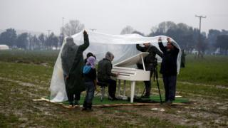 Chinese dissident artist Ai Weiwei holds a rain cover to protect a Syrian refugee woman from the rain as she plays the piano