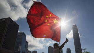 Chinese flag in front of Hong Kong skyline