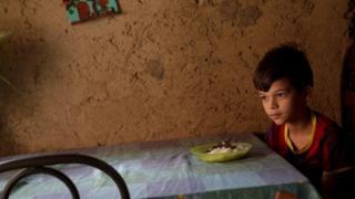 Menino venezuelano na frente de um prato de comida.