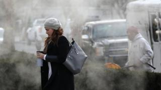 A women is bundled up as she walks past a steam grate on January 3, 2018 in Washington, DC