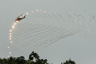 A US-made helicopter launches flares during an annual drill at the a military base.