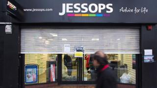 Man walks past Jessops store with shutters closed